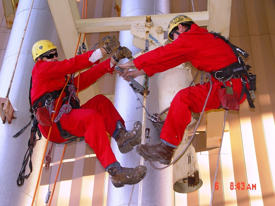 MHT Access technicians conducting maintenance on a metal structure while they are suspended by a rope access system
