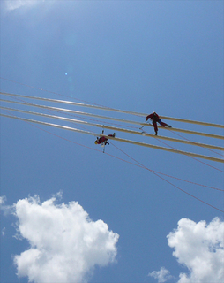 High above, a MHT rope access team easily decends down suspension cables while performing coatings maintenance work.