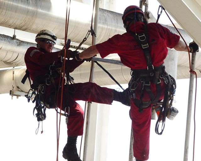 A couple of MHT rope access technicians working together on an at height project at an industrial plant.